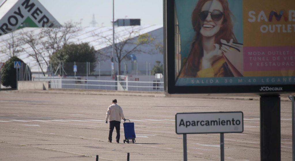Una persona arrastra un carrito en el aparcamiento de un centro comercial en Madrid